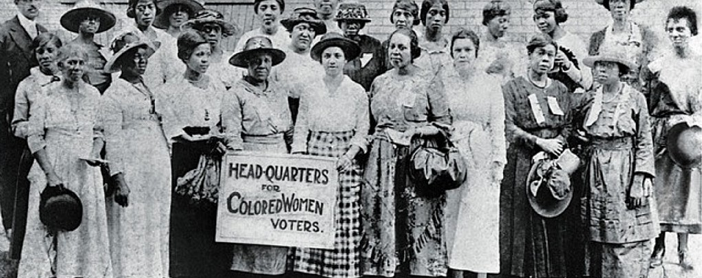 Black women suffragists meet in Georgia circa 1910-1920. Two of them hold a sign reading Head-Quarters for Colored Women Voters