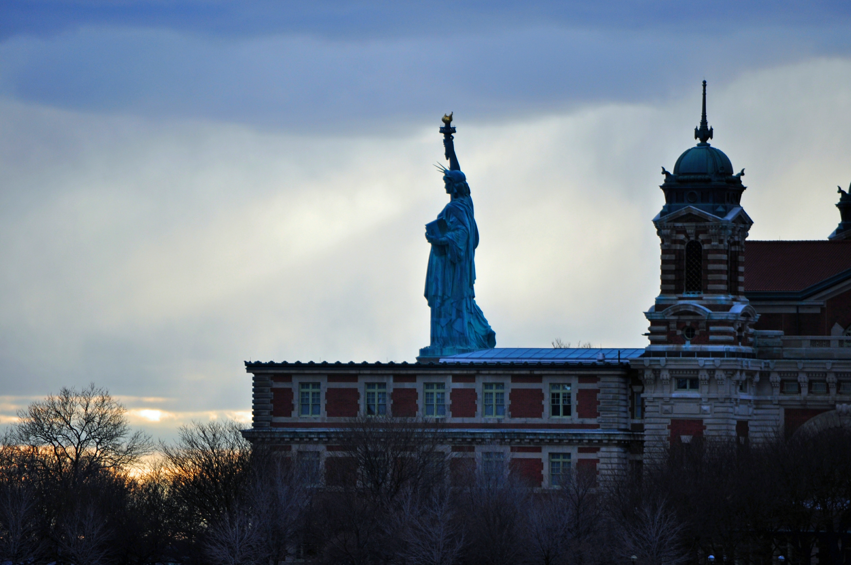 A photograph of Ellis Island with the Statue of Liberty in the background